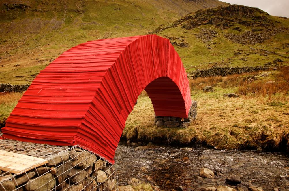 Красочный мост из бумаги с опорой из камня в сварных габионах